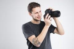 La macchina fotografica della tenuta del giovane in camicia nera ha isolato lo studio Fotografie Stock