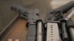 La macchina fotografica esplora un piano d'appoggio coperto di pistole e di munizioni 2 archivi video