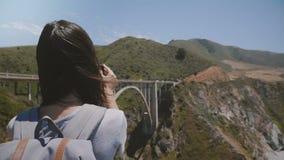 La macchina fotografica fa scorrere la destra dietro la giovane donna turistica con lo zaino che prende la foto dello smartphone  stock footage