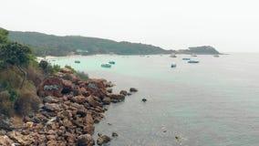 La macchina fotografica mostra le rocce della spiaggia con la baia turistica dell'oceano e dei graffiti video d archivio