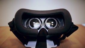 La macchina fotografica muove lento intorno ai vetri di realtà virtuale, vr, trovantesi sulla tavola, vista dai lati differenti video d archivio
