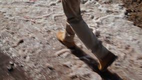La macchina fotografica persegue il piede umano che è sulla neve sporca nel pomeriggio archivi video