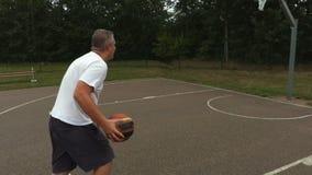 La macchina fotografica segue l'uomo con la palla di pallacanestro archivi video