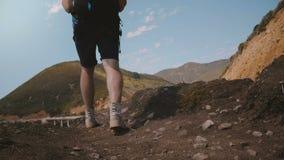 La macchina fotografica segue le gambe turistiche maschii che fanno un'escursione per guardare il paesaggio epico del punto di vi archivi video