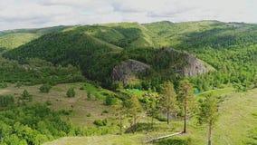 La macchina fotografica si muove attraverso l'aria, supera la collina ed offre le viste di bella valle al piede della collina archivi video