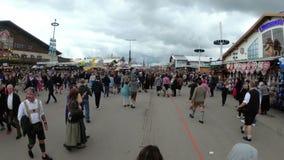 La macchina fotografica si muove da sopra la folla della gente sulla via centrale della Baviera di Oktoberfest, lasso di tempo stock footage