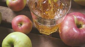 La macchina fotografica si muove su un vetro con succo fra il movimento lento delle mele stock footage
