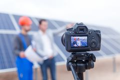 La macchina fotografica spara il lavoratore ed il direttore dei pannelli solari fotografie stock