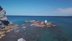 La macchina fotografica sta sorvolando il turchese e la chiara acqua di mare dalla riva e dalle rocce, vista aerea video d archivio