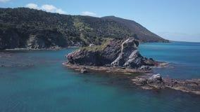 La macchina fotografica sta volando intorno alla piccola isola rocciosa in mare vicino alla riva, l'acqua del turchese del Medite video d archivio