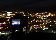 La macchina fotografica sui precedenti della città alla notte Fotografia Stock
