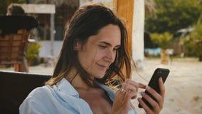 La macchina fotografica zumma sulla giovane donna caucasica felice facendo uso del riposo sorridente di compera del app dello sma stock footage