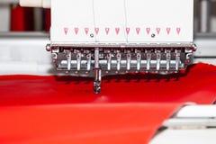 La macchina per cucire bianca industriale per ricamo annerisce il logo con la lettera S con il filo nero su un fondo rosso da immagini stock
