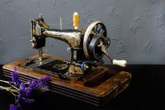 La macchina per cucire d'annata sta stando sulla tavola bianca fotografia stock libera da diritti