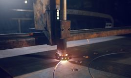 La macchina per il taglio di metalli con le scintille brucianti taglia un pezzo di lamiera sottile immagine stock