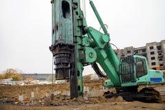 La macchina per l'accatastamento funziona ad un cantiere Fotografie Stock Libere da Diritti