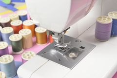 La machine à coudre et le fil coloré roule pour coudre sur le ton deux Photos libres de droits