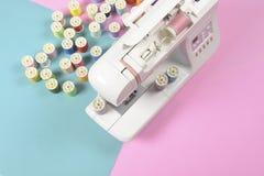 La machine à coudre et le fil coloré roule pour coudre sur le ton deux Photographie stock libre de droits