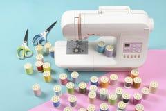 La machine à coudre et le fil coloré roule pour coudre sur le ton deux Photos stock