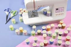 La machine à coudre et le fil coloré roule pour coudre sur le ton deux Images stock
