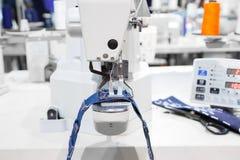 La machine à coudre traitent une couture sur le tissu de jeans Images stock