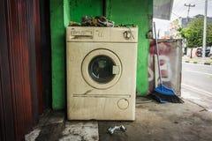La machine à laver blanche inutilisée avec l'entrée principale près du mur vert et d'une photo de balai abandonnée dans une photo Image libre de droits