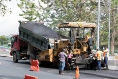 La machine d'asphalte met une nouvelle couche sur la route Image stock