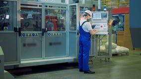 La machine d'usine est contrôlée par le spécialiste par le panneau de commande banque de vidéos