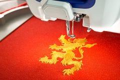 La machine de broderie et le lion d'or conçoivent sur la chemise rouge de tissu de coton, se ferment vers le haut de la photo Photographie stock