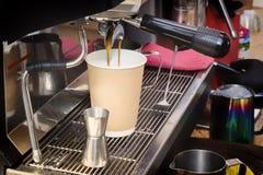La machine de café prépare le café frais et le verse dans une tasse de papier au compteur de barre image libre de droits