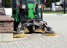 La machine de nettoyage nettoie des déchets sur des routes urbaines photo libre de droits