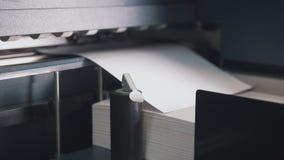La machine de presse typographique prend la feuille de papier dans l'action dans la chaîne de production d'impression photographie stock libre de droits