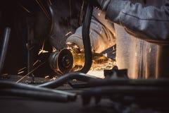 La macinazione del metallo sul tubo d'acciaio con il flash delle scintille si chiude su Fotografie Stock Libere da Diritti