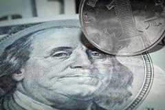 La macro de cientos monedas del billete de dólar y del yuan que ruedan sobre Franklin's observa imagen de archivo libre de regalías
