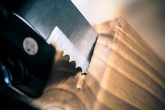 La macro de un cuchillo de filete dentado sacó parcialmente de un bloque de Knive de la cocina en una tabla imagen de archivo
