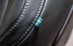 La macro fine sulla vista della bandiera dello svedese sulla sede di automobile di cuoio fotografia stock