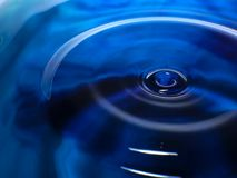 La macro photographie d'une baisse bleu-foncé de l'eau/de baisses d'encre éclaboussent et des ondulations, humide, conceptuelles  Photos stock