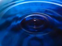La macro photographie d'une baisse bleu-foncé de l'eau/de baisses d'encre éclaboussent et des ondulations, humide, conceptuelles  Photos libres de droits