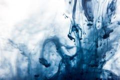La macro, pintura azul de la acuarela del extracto cae en agua con el fondo blanco Foto de archivo libre de regalías