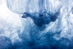 La macro, pintura azul de la acuarela del extracto cae en agua con el fondo blanco Imágenes de archivo libres de regalías