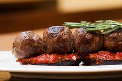 La macro vue a grillé des boulettes de viande sur des aubergines sauce tomate, romarin Un plat dans un plat blanc, fond en bois d Images stock