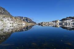 La madera del cielo azul de la naturaleza de la montaña se nubla reflejo del lago Imagenes de archivo