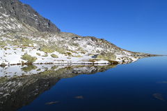 La madera del cielo azul de la naturaleza de la montaña se nubla reflejo del lago Imágenes de archivo libres de regalías