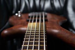 La madera del marrón de la guitarra baja foto de archivo