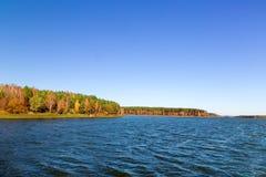 La madera del otoño en el banco del lago hermoso grande Imagen de archivo libre de regalías