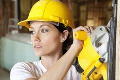 La madera femenina del corte del trabajador de construcción con un poder vio mientras que miraba lejos Imagen de archivo libre de regalías
