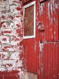 La madera resistida del granero pintó gris de descoloramiento del rojo viejo Imágenes de archivo libres de regalías