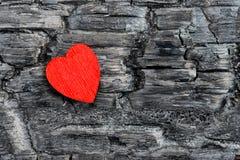 La madera roja del corazón miente en tablero quemado negro, Foto de archivo