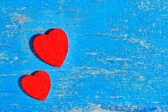 La madera roja del corazón miente en un viejo tablero de madera con la pintura azul agrietada, Imagen de archivo libre de regalías