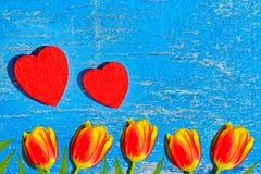 La madera roja del corazón miente en un viejo tablero de madera con la pintura azul agrietada, vintage Imágenes de archivo libres de regalías